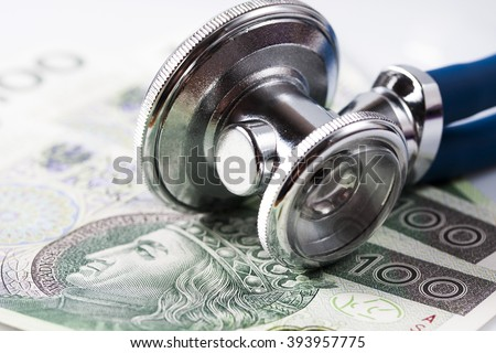 Stethoscope and polish banknotes in background - stock photo