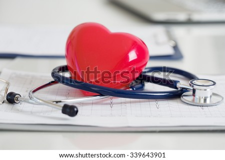 Stethoscope and red heart lying on cardiogram. Healthcare, cardiology and mediacal concept - stock photo