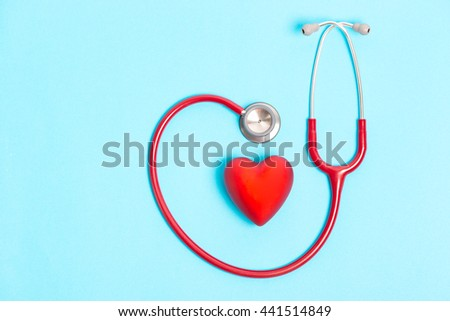 Stethoscope and red heart on blue background - stock photo