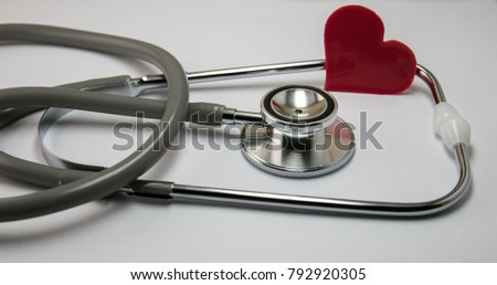 Stethoscope and red heart on table.