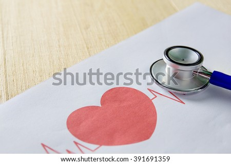 stethoscope and red heart with graph on table - stock photo