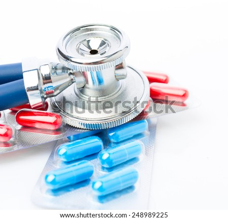 Stethoscope and some pills - isolated on a white background