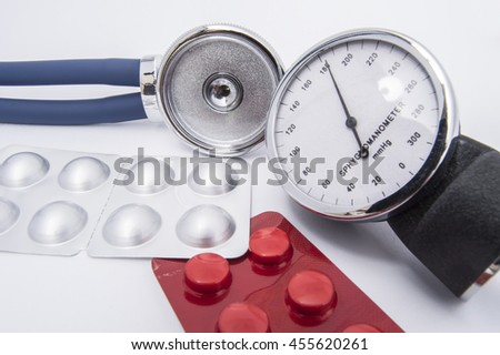 Stethoscope and sphygmomanometer dial with high indicators of arterial blood pressure lie on the white medical table near the pills and medicines in a red and chrome blister pack