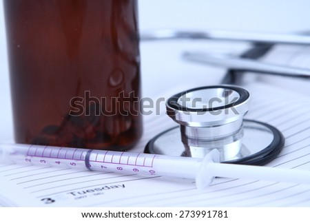 Stethoscope and syringe toned blue to emphasise medical cleanliness  - stock photo