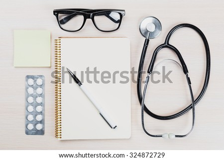Stethoscope, clipboard on wooden background