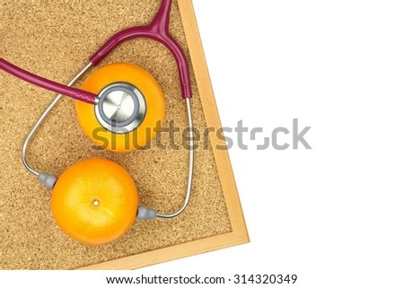 Stethoscope examining orange on a cork board. Medical equipment, Healthy food, Healthy eating concept. - stock photo