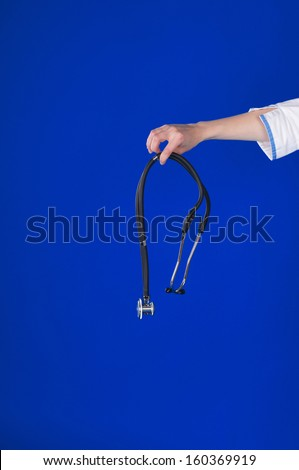 stethoscope in doctor's hand om blue background - stock photo