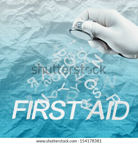 Stethoscope in hand with First aid word and crumpled paper background as medical concept - stock photo
