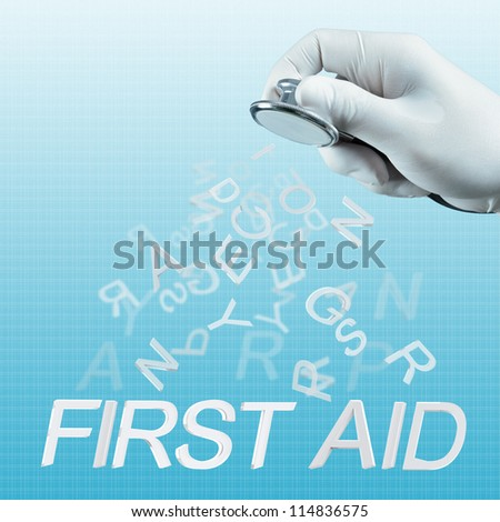 Stethoscope in hand with First aid  word as medical concept - stock photo