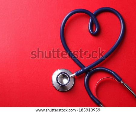 Stethoscope isolated on red background - stock photo