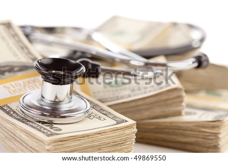 Stethoscope Laying on Stacks of Hundred Dollar Bills with Narrow Depth of Field. - stock photo