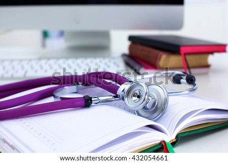 Stethoscope lying on a table on an open book - stock photo