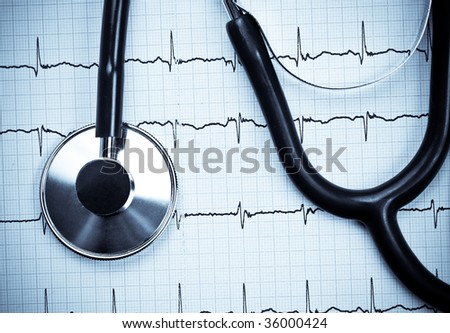 Stethoscope lying on ECG diagram - stock photo