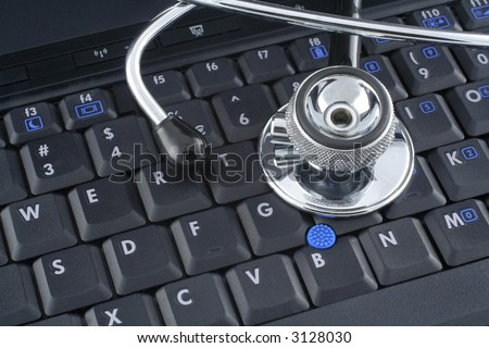stethoscope lying on keyboard of a laptop - stock photo