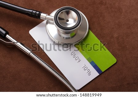 Stethoscope on a credit card concept with a brown background - stock photo