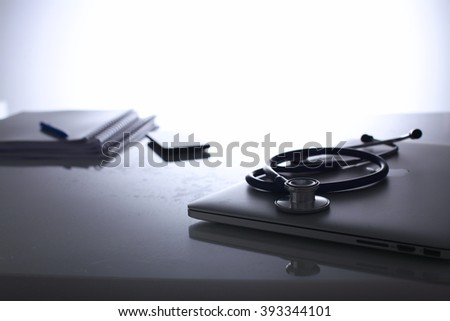 Stethoscope on a laptop computer and document - stock photo