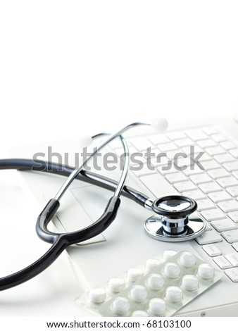 Stethoscope on a modern keyboard, isolated on white - stock photo