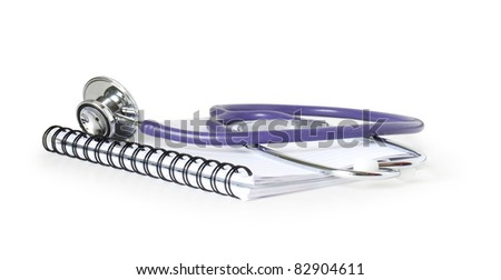 stethoscope on a notebook isolated on white - stock photo