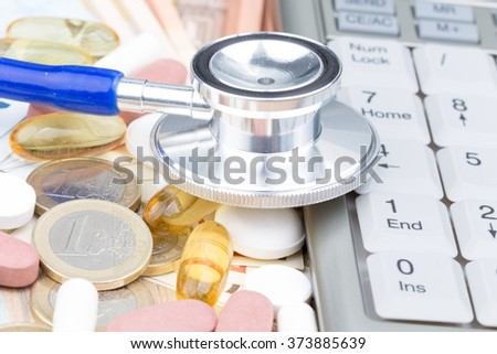 Stethoscope on a pile of money and pills with a calculator on the side - stock photo