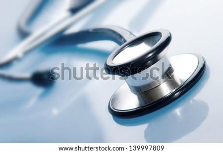 Stethoscope on blue background - stock photo