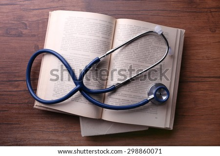 Stethoscope on books on wooden background - stock photo