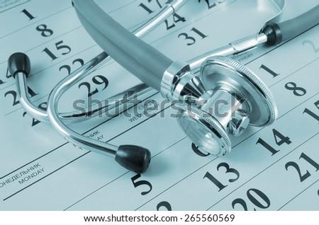Stethoscope on calendar background, regular medical examination concept - stock photo