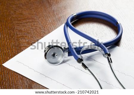 Stethoscope on cardiogram on wood desk. - stock photo