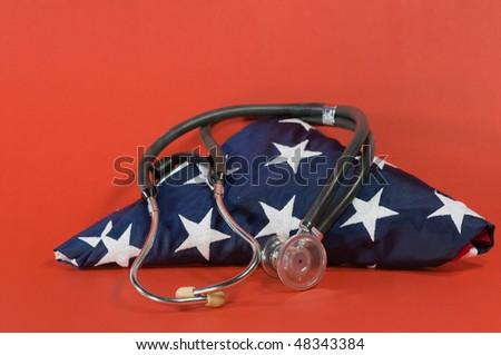 stethoscope on folded US flag with red background - stock photo