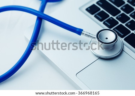 Stethoscope on laptop - Computer repair and maintenance concept - in dark tone - stock photo