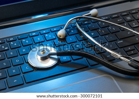 Stethoscope on laptop keyboard, blue lighting - stock photo