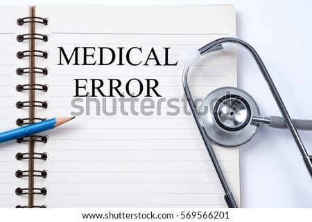 Stethoscope on notebook and pencil with Medical Error words as medical concept.