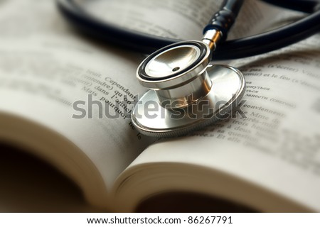 Stethoscope on open book isolated - stock photo