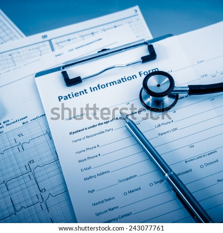 Stethoscope on patient form on the desk. - stock photo