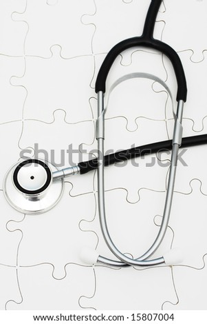 Stethoscope on puzzle, solving the mystery of health care - stock photo