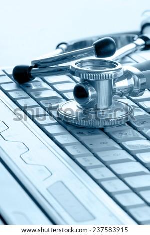Stethoscope on silver laptop - stock photo