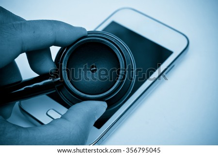 stethoscope on smartphone - checking security on smart phone concept - stock photo