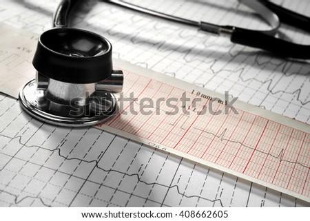 Stethoscope on the cardiogram background - stock photo