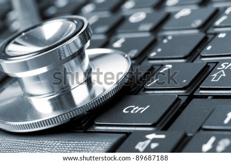 stethoscope on the laptop keyboard, close-up view, blue toned - stock photo