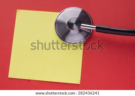 Stethoscope on top of a yellow colour paper with space for text on a red background. Concept for diet, healthcare, nutrition or medical insurance. - stock photo
