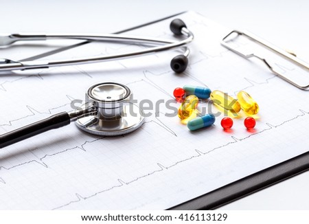 stethoscope on white background with pills and cardiogram - stock photo