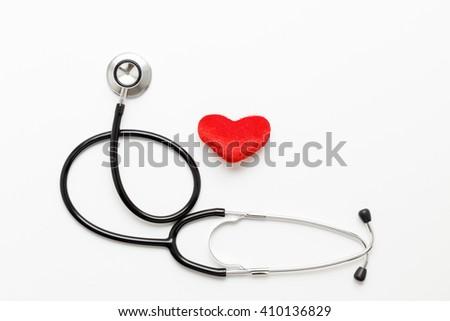 stethoscope on white background with plush heart - stock photo