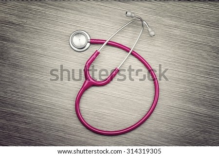 Stethoscope on wood background, Medical equipment. (Vintage Style Color) - stock photo