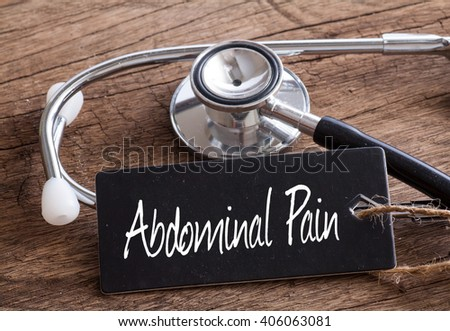 Stethoscope on wood with Abdominal Pain words as medical concept - stock photo