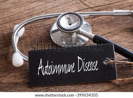 Stethoscope on wood with Autoimmune Disease words as medical concept - stock photo