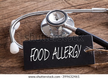 Stethoscope on wood with Food Allergy word as medical concept