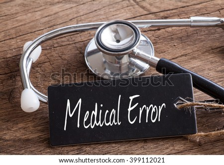 Stethoscope on wood with Medical Error word as medical concept - stock photo