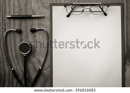 stethoscope on wooden paper glasses - stock photo