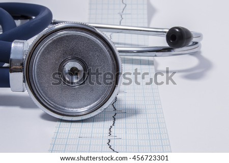 Stethoscope or phonendoscope is on the tape with the recorded electrocardiogram (EKG or ECG)  front view. The idea for the cardiological or general medical examination or checkup - stock photo