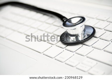 Stethoscope over a computer keyword for a modern medical concept - stock photo
