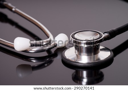 Stethoscope over a dark reflective background / Stethoscope